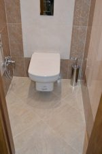 Туалет бежевый – Туалет с темно-бежевой плиткой по периметру и с подвесным унитазом в центре » Дизайн туалета в фото